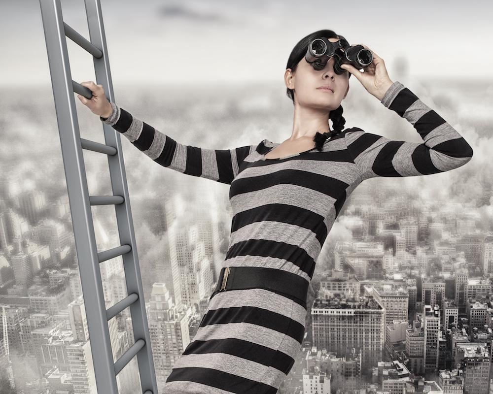 Femme d'affaires dans une échelle regardant au loin avec des jumelles