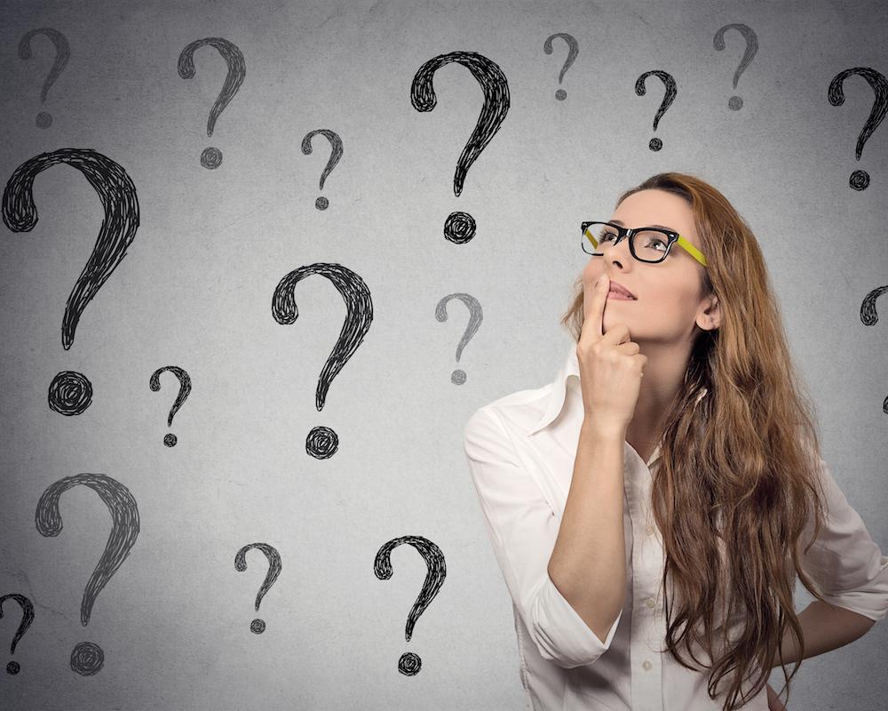 Femme d'affaires en réflexion regardant vers le haut plusieurs points d'interrogation reproduits sur un mur gris